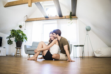 Affectionate couple sitting on the floor at home - JOSF02630