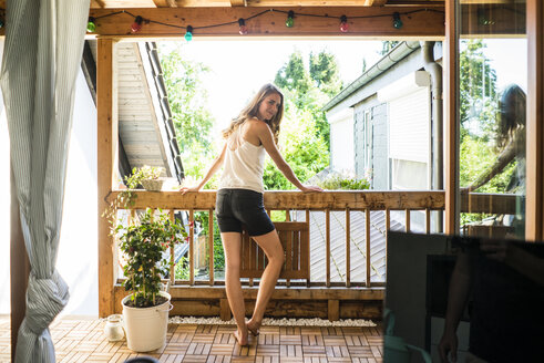 Portrait of smiling woman standing on balcony - JOSF02645