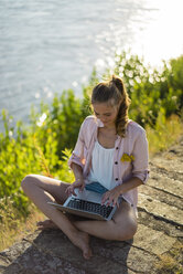 Woman sitting at the riverside in summer using laptop - JOSF02669
