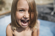 Portrait of screaming little girl having fun in pool - KMKF00445