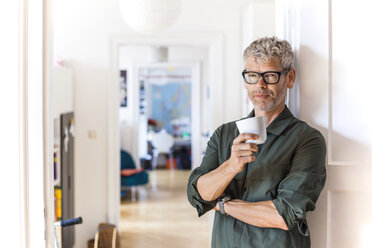 Portrait of mature man with cup of coffee leaning against door case at home - TCF05811