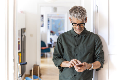Mature man leaning against door case at home using cell phone - TCF05814