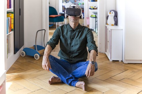 Mature man sitting on the floor at home using Virtual Reality Glasses - TCF05817