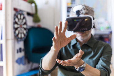 Portrait of mature man at home using Virtual Reality Glasses - TCF05820