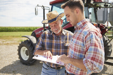 Two farmers looking at data from clipboard on the farm - ABIF00939
