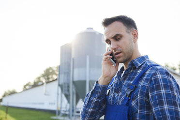 Farmer talking on cell phone on field - ABIF00960