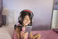 Portrait of little girl listening music with  headphones and smartphone on bed - JASF01925