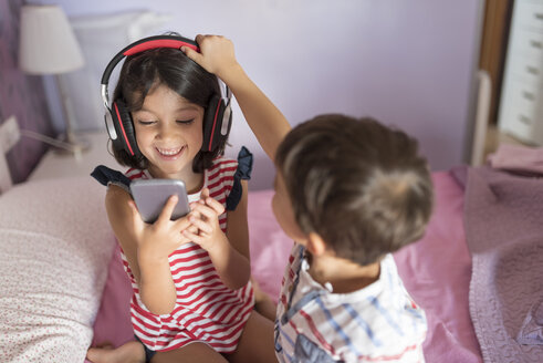 Portrait of smiling girl listening music with headphones while her little brother disturbing her - JASF01928