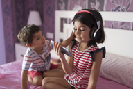 Portrait of smiling girl listening music with headphones while her little brother disturbing her - JASF01931