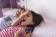 Siblings lying on bed at home playing together - JASF01934