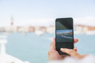 Italy, Venice, close-up of tourist taking a smartphone picture from the city - JUNF01206