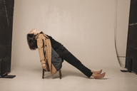 Woman sitting outstretched on chair in a photographic studio - KMKF00455