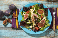 Mixed salad with figs, tomatoes, sheep cheese, grissini with ham on plate - MAEF12734