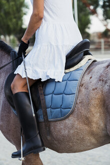 Woman riding on horse, partial view - KKAF01576