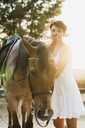 Portrait of smiling woman standing besides riding horse at backlight - KKAF01588