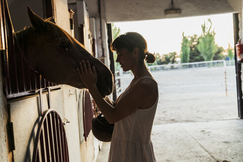 Woman stroking horse in stable - KKAF01594