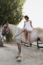 Barefoot woman sitting bareback on horse - KKAF01603