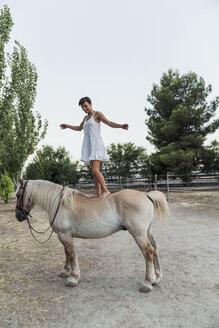 Smiling woman balancing barefoot on horseback - KKAF01615