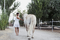 Smiling woman in white dress leading horse - KKAF01618