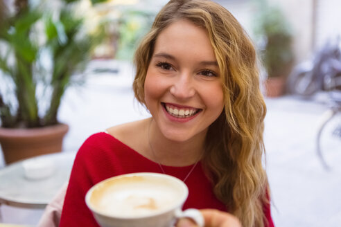 Portrait of laughing young woman with tea cup at pavement cafe - MGIF00236