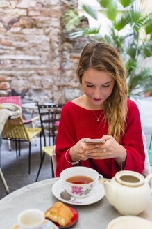 Young woman sitting at pavement cafe using smartphone - MGIF00239