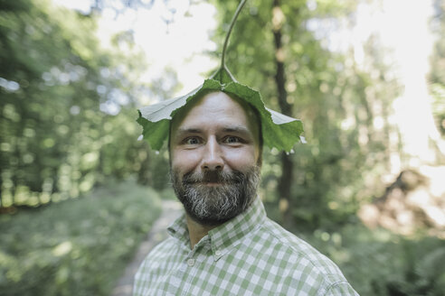 Portrait of smiling man with leaf on his head - KMKF00461