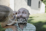 Portrait of smiling mature man with daisies in his beard playing with little daughter in the garden - KMKF00470