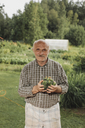 Portrait of content senior man with handfull of cucumbers in his garden - KMKF00473