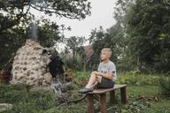 Boy relaxing on wooden bench in the garden - KMKF00476