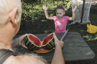 Portrait of little girl in the garden with her grandfather slicing watermelon - KMKF00479