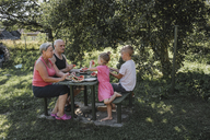 Grandparents spending time together with grandson and granddaughter in the garden eating watermelon - KMKF00482