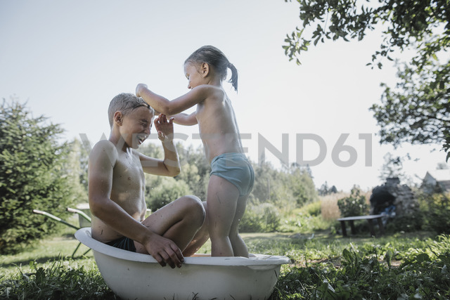 Brother and sister playing with water in little bath tub in garden - KMKF00494