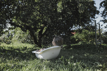 Little girl relaxing in bath tub in garden - KMKF00497