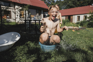 Happy brother and sister playing with water in garden - KMKF00503