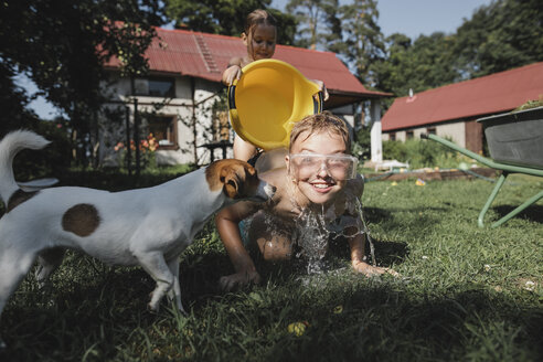 Brother, sister and dog playing with water in garden - KMKF00506