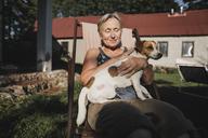 Smiling senior woman with dog on deckchair in garden - KMKF00509