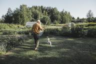 Senior man playing with dog in garden - KMKF00512