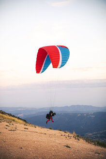 Paraglider starting to fly with mountains in the background - ACPF00316