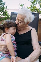 Grandmother kissing her granddaughter on terrace - GEMF02372