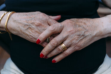 Hands of senior woman with golden rings and red painted nails - GEMF02384