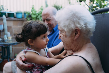 Grandparents and granddaughter spending time together on the terrace - GEMF02387