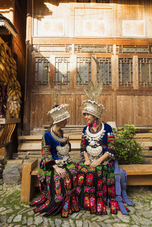 China, Guizhou, two smiling young Miao women wearing traditional dresses and headdresses - KKAF01627