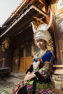 China, Guizhou, portrait of a young Miao woman wearing traditional dress and headdress - KKAF01630