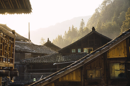 China, Guizhou, houses of a Miao settlement in backlight - KKAF01636