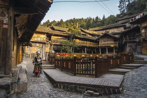 China, Guizhou, young Miao woman in traditional dress walking in a settlement - KKAF01639
