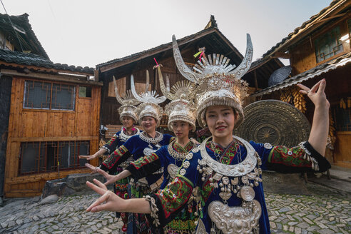 China, Guizhou, Miao women wearing traditional dresses and headdresses posing on village square - KKAF01645