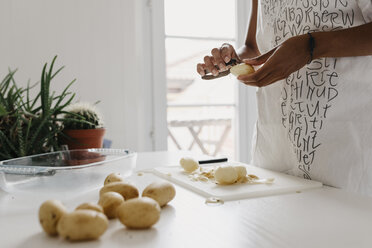 Woman preparing potatoes in the kitchen, partial view - LHPF00001