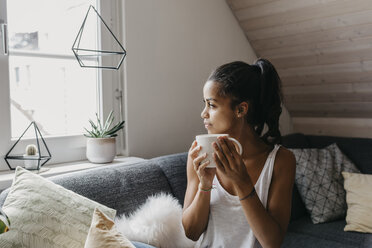 Young woman with cup of coffee sitting on the couch at home looking out of window - LHPF00010