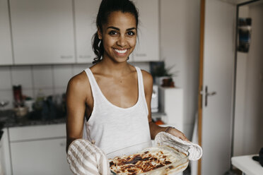 Portrait of smiling young woman with casserole in the kitchen - LHPF00019