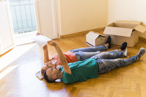 Happy couple lying side by side on the floor of new home looking together at contract - FBAF00016